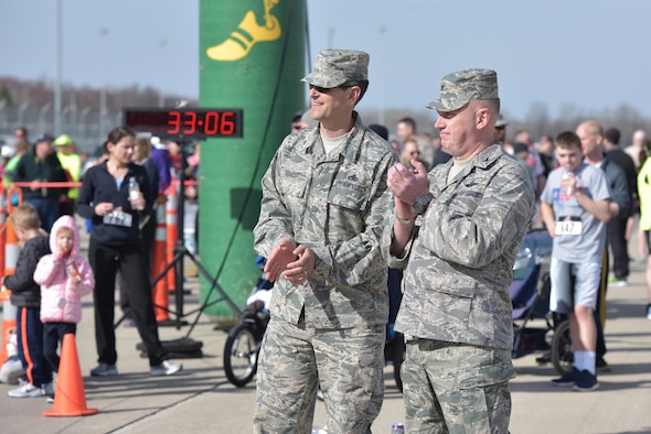 U.S. Air Force Col. Kevin Doyle, commander of the 180th Fighter Wing, Ohio Air National Guard and Chief Master Sgt. John Deraedt, command chief master sergeant assigned to the wing, cheer on runners as they finish the I Believe I Can Fly 5k race at the Toledo Express Airport in Swanton, Ohio on April 9, 2017. The wing's Company Grade Officer Council partnered with the non-profit organization, The Arms Forces, as well as local law enforcement, fire departments and civilian volunteers to hold the third annual race which had approximately 270 participants, to raise awareness for military members with post-traumatic stress disorder and traumatic brain injury. The race, now in its third year, provides runners of all ages, the rare opportunity to run a unique course, down the taxiways used by Northwest Ohio's very own 180FW, while also promoting awareness and raising funds to benefit our veterans who have given so much to our great nation. (U.S. Air National Guard photo by Tech. Sgt. Nic Kuetemeyer)