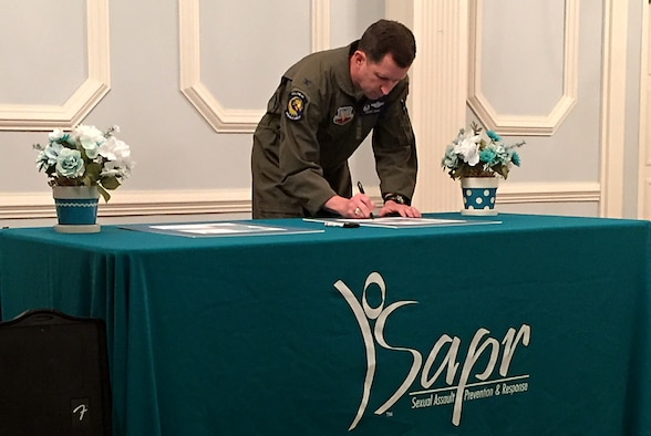 "Col. Christopher Sage, 4th Fighter Wing commander, signs a Sexual Assault Prevention and Response Proclamation during a SAPR seminar, April 3, 2017, at Seymour Johnson Air Force Base, North Carolina. The 2017 Sexual Assault Awareness and Prevention Month theme is, ""Protecting Our People Protects Our Mission."" (Courtesy photo)"