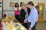 Defense Logistics Agency Installation Support at Richmond held a ceremony, April 3, 2017, for the reopening of the Bettye Akermann Cobb Child Development Center on Defense Supply Center Richmond, Virginia. In celebration David Gibson, right, director of DLA Installation Support at Richmond, and the DLA Installation Support's Director Denise Miller, center, cut the cake as CCD Director Casey Chapman, back left, and Family Morale and Wellness Director Ursula Hickox, back right, share in the celebration.