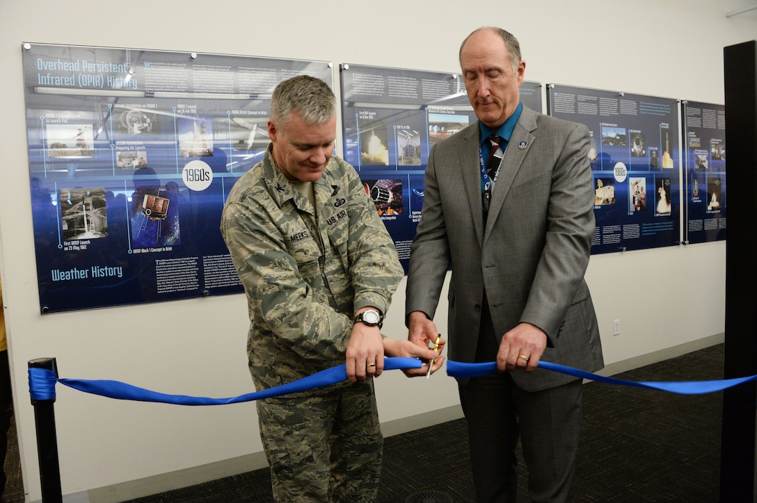 Col. Tony Meeks, deputy director of the Space and Missile Systems Center's Remote Sensing Systems Directorate, and Dr. Steve Pluntze, RS Directorate executive director and civilian deputy director, cut a ceremonial ribbon to unveil the Remote Sensing Heritage Wall at Los Angeles Air Force Base in El Segundo, Calif., March 15, 2017. The ceremony commemorates an SMC mission that spans nearly six decades of providing global, persistent, infrared surveillance and environmental monitoring capabilities to our warfighters and the nation. (U.S. Air Force photo / Van De Ha)