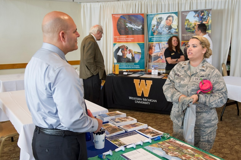 Second Lt. Leah Vincuilla, 45th Force Support Squadron sustainment services deputy flight commander, engages in conversation with a representative from Regent University, during an Education Fair at Patrick Air Force Base, Fla. April 4, 2017. The event was designed to open doors for military, civilians, and family members to explore educational and certification programs available to them from participating schools and vendors. (U.S. Air Force photo by Derwin Oviedo)