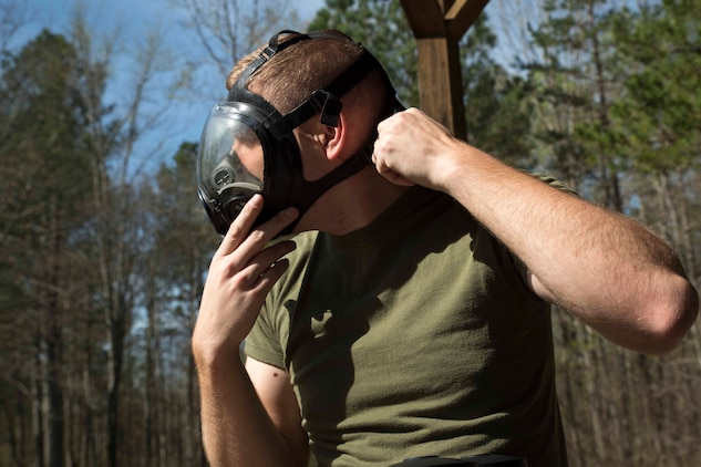 TUNNEL HILL, Ga. - Lance Cpl. Tyler Kuehn, a hazmat technician with Chemical Biological Radiological Nuclear Platoon, Combat Logistics Regiment 4, 4th Marine Logistics Group, Marine Forces Reserve, adjusts his gas mask during a CBRN training exercise at Volunteer Training Site, Catoosa, Tunnel Hill, Ga., April 4, 2017. The CBRN Marines check their masks every time they put on any of their suits to ensure their mask will provide clean oxygen for up to an hour while they are in an unknown area. (U.S. Marine Corps photo by Cpl. Devan Alonzo Barnett/Released)