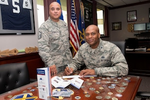 Col. Roy Collins, 37th Training Wing commander (seated) signs a contribution slip for the Air Force Assistance Fund as Master Sgt. Joseph Aponte, 323rd Training Squadron military training instructor and project officer for the 37th TRW AFAF campaign, looks on April 10, at Joint Base San Antonio-Lackland. The AFAF campaign is comprised of four charities, Air Force Villages Inc., Air Force Aid Society Inc., Air Force Enlisted Village Inc. and the General and Mrs. Curtis E. LeMay Foundation, which solely assists active duty, reserve and retired Airmen and their families. The various charities provide low to no-cost retirement homes for Airmen and family members, emergency funds and travel arrangements, scholarships, grants and more. (U.S. Air Force photo by Staff Sgt. Marissa Garner)