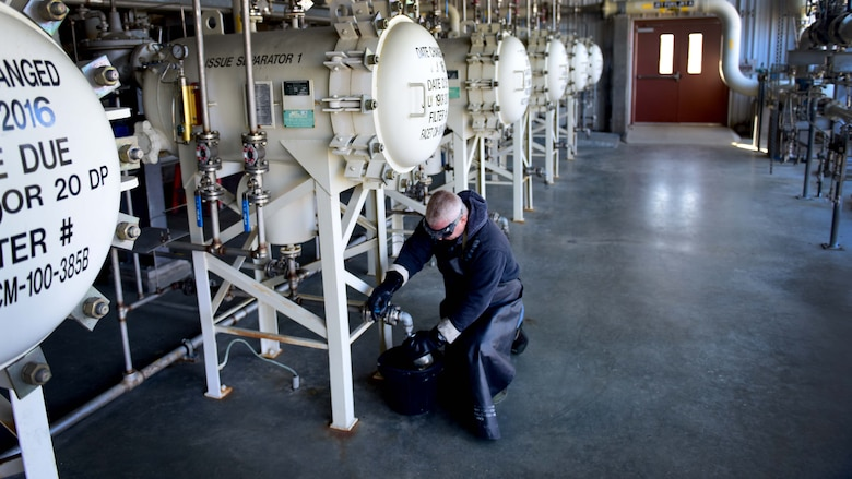 Darryl Hodge, 733rd Logistics Readiness Squadron fuels facilities fuels distribution systems operator, takes a fuel sample at Joint Base Langley-Eustis, Va., April 10, 2017. Much like liquid oxygen, many steps are taken to ensure quality jet fuel is used to power aircraft on base, to include checking the tank that is currently in use, every 24 hours for water. (U.S. Air Force photo/Staff Sgt. Areca T. Bell)