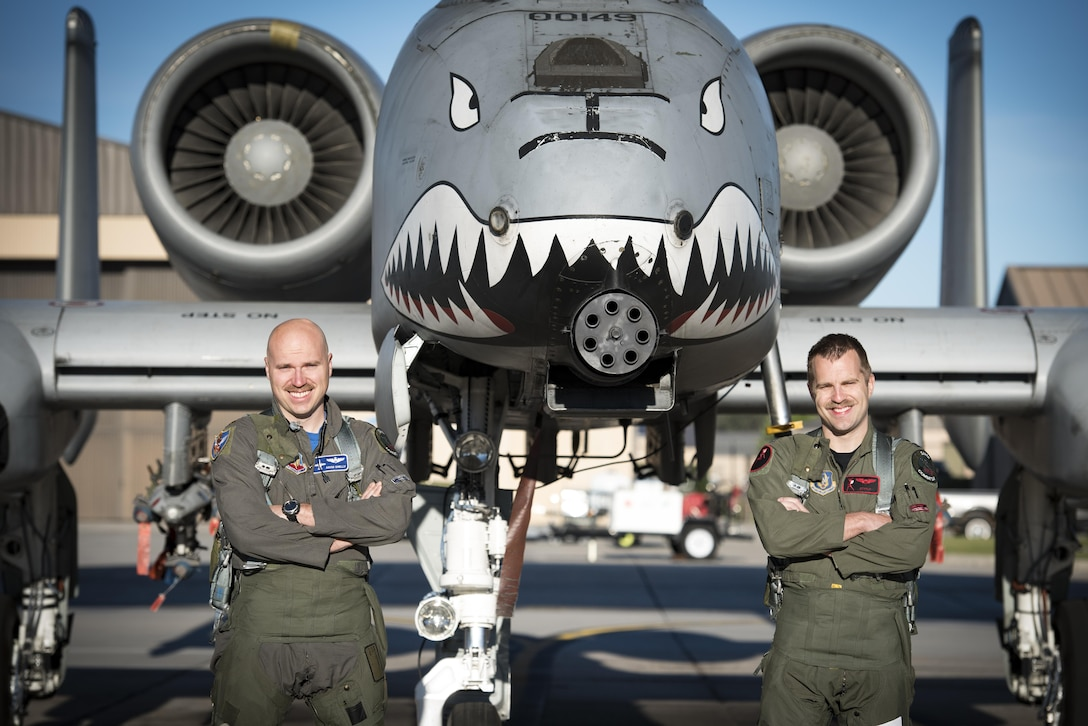 Maj. Matthew Shelly, 23 Wing director of inspections, left, and Capt. Christopher Shelly, 76th Fighter Squadron chief of standards and evaluations, pose for a photo with an A-10C Thunderbolt II, April 8, 2017, at Moody Air Force Base, Ga. The brothers flew in formation together for the first time, fulfilling their childhood dream while also contributing to total force integration, the use of multiple components of the Air Force, which can include active duty, reserve or guard. (U.S. Air Force photo by Airman 1st Class Lauren M. Sprunk)