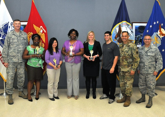 """Senior leaders pose with """"Ladies DSW 2.0,"""" the first-place team, at the 2017 Winter Warrior Project awards ceremony, April 12, 2017, Fort Belvoir, Virginia. From left: DLA Director Air Force Lt. Gen. Andy Busch; Anita Elum-Mason; Rowena Estrada; Ahawana Williams; Christina Darensbourg; team coach Demetrios Danis; Army Command Sgt. Major Charles Tobin, DLA senior enlisted leader; Air Force Chief Master Sgt. Timothy Horn, DTRA senior enlisted leader."""