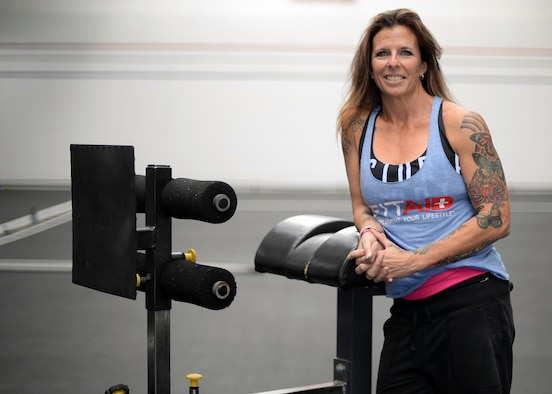 Sherri Biringer, 56th Force Support Squadron fitness specialist supervisor, poses next to an ab workout machine Apr. 1, 2017 at the Combat Fitness Center in Luke Air Force Base, Ariz. Biringer is a certified CrossFit instructor and trains Airmen on achieving their physical goals. (U.S. Air Force photo by Senior Airman Devante Williams)