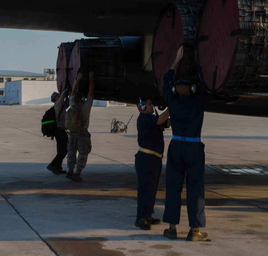 Ground crews remove the engine covers from a B-1 Lancer prior to startup at Boca Chica Naval Air Station, Key West Fla., March 23, 2017. These covers protect aircraft from Foreign Object Damage and severe weathering. The long range, multi-role bomber uses four General Electric F101-GE-102 turbofan engine with afterburner that produce more than 30,000 pounds of thrust, per engine allowing the bomber to reach speeds of Mach 1.25. (U.S. Air Force photo by Staff Sgt. Jason McCasland/released)