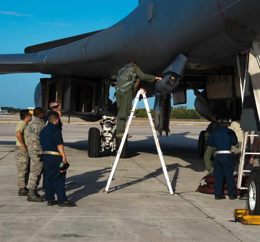 """Col. Justin Boldenow, 7th Operations Group commander, inspects a targeting pod on a B-1 Lancer at the Boca Chica Naval Air Station, Key West Fla., March 24, 2017.  This targeting pod is capable of tracking, targeting and engaging moving targets. The Joint Interagency Task Force South used the B-1 to track drug smugglers """"go-fast"""" boats across more than 3.2 million square miles of ocean.(U.S. Air Force photo by Staff Sgt. Jason McCasland/released)"""