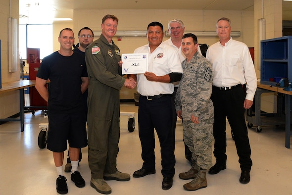 "Edwardo De La Paz, 47th Maintenance Directorate aircrew egress shop supervisor (center), accepts the ""XLer of the Week"" award from Col. Thomas Shank, 47th Flying Training Wing commander (left), and Chief Master Sgt. George Richey, 47th FTW command chief (right), on Laughlin Air Force Base, Texas, April 4, 2017. The XLer is a weekly award chosen by wing leadership and is presented to those who consistently make outstanding contributions to their unit and Laughlin. (U.S. Air Force photo/Airman 1st Class Daniel Hambor)"