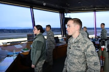 62nd Operations Support Squadron Air traffic Controllers look on at the McChord Field flight line from the tower on April 11, 2017, on Joint Base Lewis-McChord, Wash. Their job is to separate aircraft in the air and on the ground and ensure everyone's safety all while getting the aircraft in and out as quickly as possible from the air field. (Air Force Photo/ Staff Sgt. Naomi Shipley)