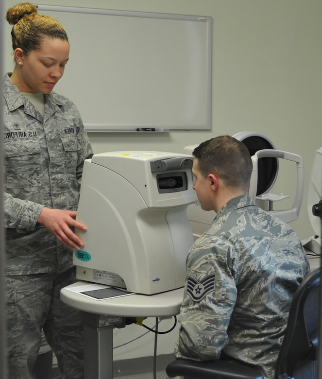 U.S. Air Force Senior Airman Kiara Warren, 51st Aerospace Medicine Squadron optometry technician, left, operates the non-contact tonometer while Staff Sgt. River Carson, 8th Medical Operations Squadron public health technician, applies his forehead to the machine at Kunsan Air Base, Republic of Korea, March 24, 2017. The non-contact tonometer checks the pressure of the eye by blowing air into the eye to flatten the cornea to measure intraocular pressure. (U.S. Air Force photo by Senior Airman Colville McFee/Released)