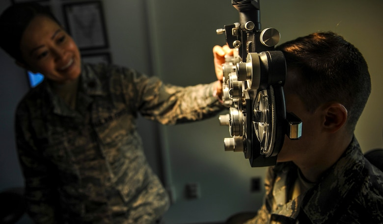 U.S. Air Force Maj. See Vang, 51st Aerospace Medicine optometry flight commander, left, changes lenses on the phoropter while Staff Sgt. River Carson, 8th Medical Operations Squadron public health technician, stares at a letter chart on at Kunsan Air Base, Republic of Korea, March 24, 2017. The phoropter checks for refractive errors in the eyes and assists in eye glass prescriptions.  (U.S. Air Force photo by Senior Airman Colville McFee/Released)