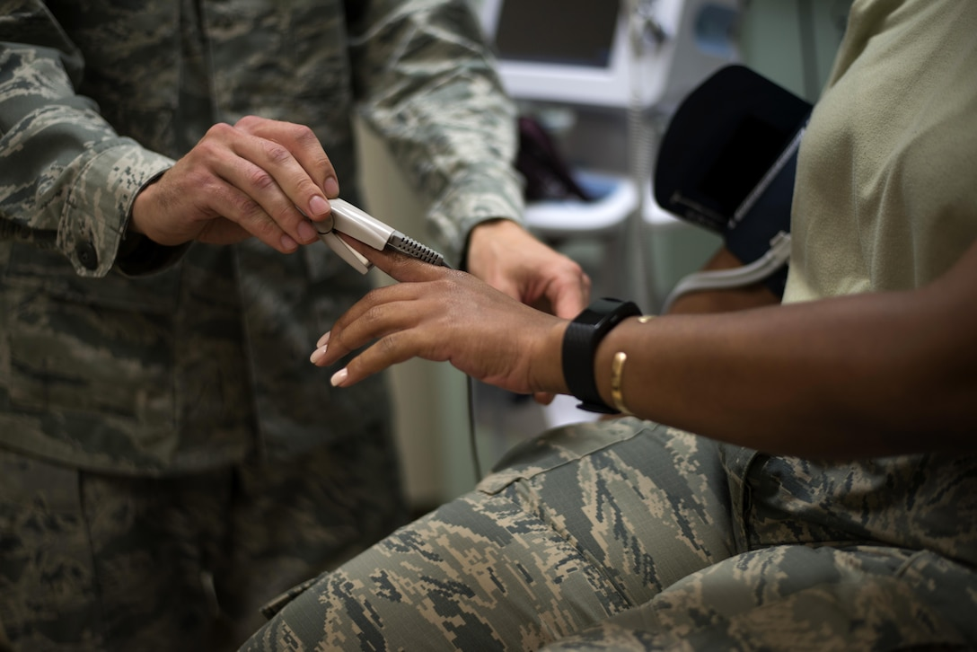 U.S. Air Force Staff Sgt. Aliaksei Krasouski, a medical technician assigned to the 91st Air Refueling Squadron, attaches a machine to monitor the heart rate of a patient March 8, 2017, at MacDill Air Force Base, Fla. Krasouski joined the Air Force after emigrating from Minsk, Belarus. (U.S. Air Force Photo by Airman 1st Class Rito Smith)