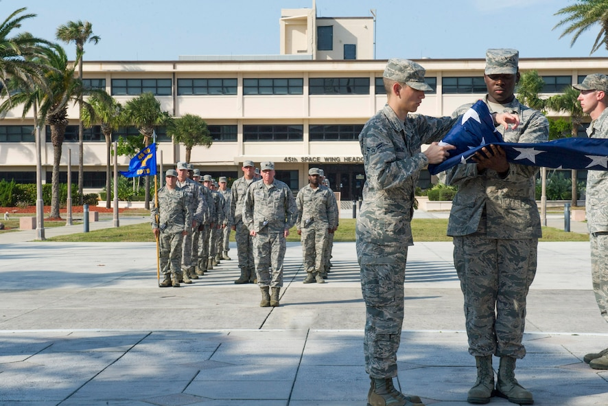 Airmen fold the flag as 45th Space Wing members stand in formation during a wing retreat April 5, 2017, at Patrick Air Force Base, Fla. The wing holds retreat quarterly to show its respect to the Stars and Stripes. (U.S. Air Force Photo by Phil Sunkel)