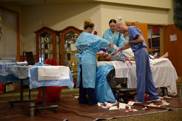 """Maj. Hans Watson, emergency room doctor, checks for signs of life on drunken driving victim while Tech. Sgt. Lauren Pelkey uses a handheld resuscitator and Airman 1st Class Yolanda Alvarez Hernandez performs chest compressions April 12, 2017, at the Grizzly Bend at Malmstrom Air Force Base, Mont. The event was part of """"Live or Die,"""" a production helping members think about consequences before they get behind the wheel intoxicated. (U.S. Air Force photo\ Staff Sgt. Lindsey Soulsby)"""