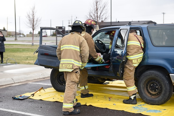 """Firefighters remove an Airman acting as a drunken driving victim from a vehicle April 12, 2017, at the Grizzly Bend at Malmstrom Air Force Base, Mont. The event was part of """"Live or Die,"""" a production helping members think about consequences before they get behind the wheel intoxicated. (U.S. Air Force photo\ Staff Sgt. Lindsey Soulsby)"""