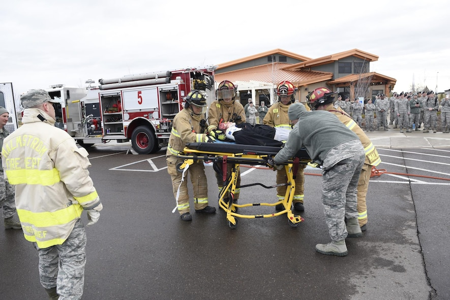 """Malmstrom Airmen watch as firefighters transfer an Airman acting as a drunken driving victim to a gurney April 12, 2017, at the Grizzly Bend at Malmstrom Air Force Base, Mont. The event was part of """"Live or Die,"""" a production helping members think about consequences before they get behind the wheel intoxicated. (U.S. Air Force photo\ Staff Sgt. Lindsey Soulsby)"""