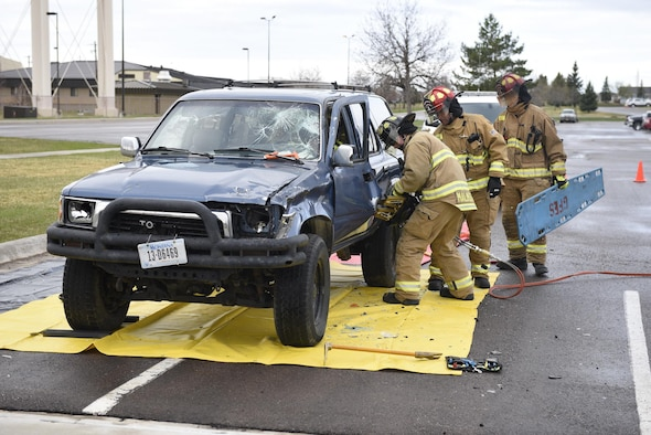 """Firefighters use a hydraulic rescue tool to remove an Airman acting as a drunken driving victim from a vehicle April 12, 2017, at the Grizzly Bend at Malmstrom Air Force Base, Mont. The event was part of """"Live or Die,"""" a production helping members think about consequences before they get behind the wheel intoxicated. (U.S. Air Force photo\ Staff Sgt. Lindsey Soulsby)"""