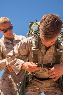 U.S. Marine Lance Cpl. Connor Honeycutt assists Lance Cpl. Avery Wells with adjusting his parachute during Weapons and Tactics Instructors Course 2-17 on Marine Corps Air Station, Yuma, Ariz., March 30, 2017. Static line parachute training is used to develop Marines' efficiency with the equipment. Honeycutt is an air delivery specialist with Landing Support Company, 1st Transportation Support Battalion, Combat Logistics Regiment 1, 1st Marine Logistics Group and Wells is an air delivery specialist with Landing Support Company, 1st TSB, CLR-1, 1st MLG. (U.S. Marine Corps photo by Lance Cpl. Roderick Jacquote)