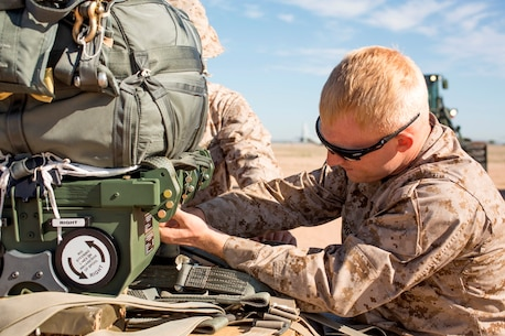 U.S. Marine Lance Cpl. Chancy Rogers adjusts the settings on a Joint Precision Airdrop System during Weapons and Tactics Instructors Course 2-17 on Marine Corps Air Station, Yuma, Ariz., March 30, 2017. The JPADS uses GPS, a modular autonomous guidance unit, a parachute and electric motors to guide cargo to their targeted drop zones. Rogers is an air delivery specialist with Landing Support Company, 2nd Transportation Support Battalion, 2nd Combat Logistics Regiment, 2nd Marine Logistics Group. (U.S. Marine Corps photo by Lance Cpl. Roderick Jacquote)