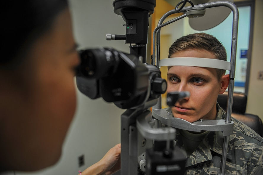 U.S. Air Force Maj. See Vang, 51st Aerospace Medicine Squadron optometry flight commander, left, scans the eye of Staff Sgt. River Carson, 8th Medical Operations Squadron public health technician, using the slit lamp during his eye exam at Kunsan Air Base, Republic of Korea, March 24, 2017. The slit lamp uses an intense beam of light to show the eye in detail to check for abnormalities during eye checkups. (U.S. Air Force photo by Senior Airman Colville McFee/Released)