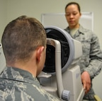U.S. Air Force Staff Sgt. River Carson, 8th Medical Operations Squadron public health technician, applies his forehead to the auto refractometer as Senior Airman Kiara Warren, 51st Aerospace Medicine Squadron optometry technician, operates the machine at Kunsan Air Base, Republic of Korea, March 24, 2017. The auto refractometer measures the curvature of the eye and allows a scan to give a baseline prescription for eyes. (U.S. Air Force photo by Senior Airman Colville McFee/Released