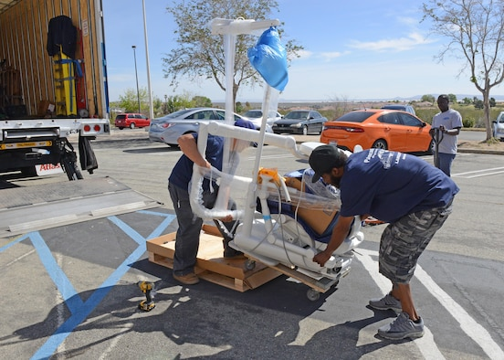 Deliverymen prepare to move one of 15 new dental chairs into the 412th Medical Group Dental Clinic April 6. (U.S. Air Force photo by Kenji Thuloweit)