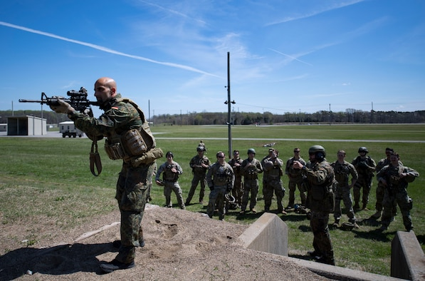 German Air Force Maj. Nader Samadi, German Air Ground Operations Squadron commander demonstrates the different stances Airmen must shoot from to successfully complete the shooting portion of a German armed forces proficiency assessment, April 4, 2017, at Fort Campbell, Ky. To enhance their ability to work together in deployed locations, members of the German Air Force travelled to Fort Campbell to train and exercise with the 19th ASOS. While at Fort Campbell, The German Air Force members hosted a German armed forces proficiency assessment for Airmen consisting of shooting firearms, swimming, agility exercises and a rucksack march.
