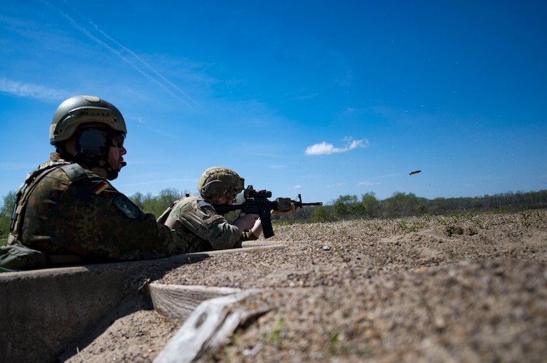German Air Force 1st Lt. Marco Bruck, German Air Ground Operations Squadron Joint Terminal Attack Controller evaluator, left, observes while U.S. Air Force Senior Airman Brandon Malinowski, 19th Air Support Operations Squadron Tactical Air Control Party specialist fires during the shooting portion of a German armed forces proficiency assessment, April 4, 2017, at Fort Campbell, Ky. To enhance their ability to work together in deployed locations, members of the German Air Force travelled to Fort Campbell to train and exercise with the 19th ASOS. While at Fort Campbell, The German Air Force members hosted a German armed forces proficiency assessment for Airmen consisting of shooting firearms, swimming, agility exercises and a rucksack march.