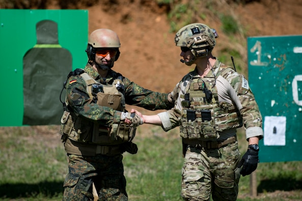 German Air Force Maj. Nader Samadi, German Air Ground Operations Squadron commander left, congratulates U.S. Air Force Ryan Hawkins 19th Air Ground Operations Squadron Tactical Air Control Party specialist, during the shooting portion of a German armed forces proficiency assessment, April 4, 2017, at Fort Campbell, Ky. To enhance their ability to work together in deployed locations, members of the German Air Force travelled to Fort Campbell to train and exercise with the 19th ASOS. While at Fort Campbell, The German Air Force members hosted a German armed forces proficiency assessment for Airmen consisting of shooting firearms, swimming, agility exercises and a rucksack march.