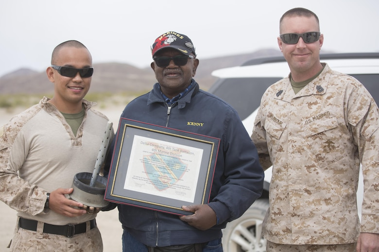 Capt. Christopher J. Silva, inspector-instructor, and Master Sgt. Ryan Barbour, tank leader, of Company D, 4th Tank Battalion, presented a plaque to retired U.S. Marine Corps Staff Sgt. Kenneth R. White at Range 500 during a visit to Marine Corps Air Ground Combat Center, Twentynine Palms, Calif., Sunday. 4th Tanks invited White aboard the Combat Center because they wanted to honor his last wish as a former tanker. (U.S. Marine photo by Lance Cpl. Natalia Cuevas)