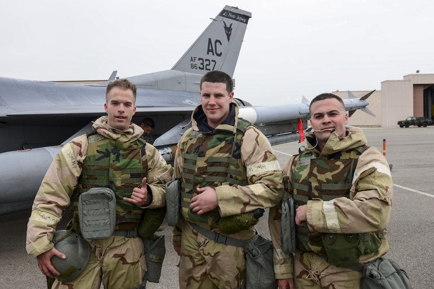 U.S. Air Force Staff Sgt. Jon Bybee and U.S. Air Force Senior Airmen Charles Michel and Andrew Finnegan, 177th Aircraft Maintenance Squadron weapons load crew members, pose in front of an F-16 Fighting Falcon at Osan Air Base, Republic of Korea, April 14, 2017. The Airmen are deployed to Osan from the New Jersey Air National Guard's 177th Fighter Wing, competed against their active duty counterparts in the 51st Maintenance Group's quarterly weapons load crew competition. (U.S. Air Force photo by Staff Sgt. Victor J. Caputo)