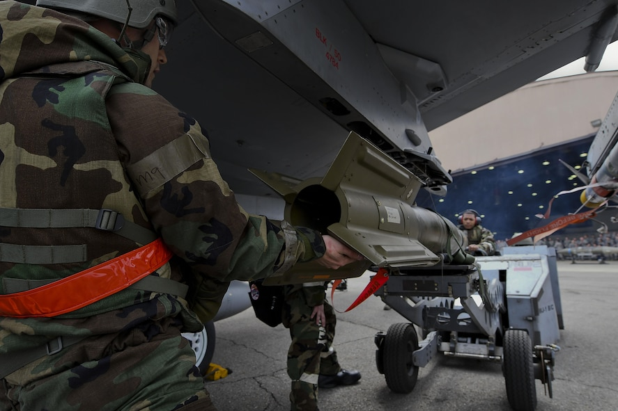 Members of the 36th Aircraft Maintenance Unit compete in a quarterly 51st Maintenance Group weapons load competition at Osan Air Base, Republic of Korea, April 14, 2017. During the competition each team was responsible for loading an AIM-9 Sidewinder, GBU-38 Joint Direct Attack Munition, and GBU-12 Paveway II onto an aircraft frame in a timely manner. (U.S. Air Force photo by Airman 1st Class Gwendalyn Smith)