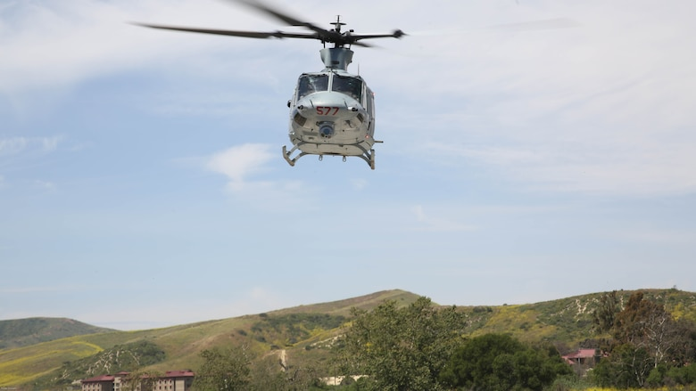 A UH-1Y Huey with Marine Light Attack Helicopter Training Squadron 303 flies over Marines with School of Infantry West during an aerial demonstration at Marine Corps Base Camp Pendleton, Calif., April 11. Marines with HMLAT-303 conducted basic flight maneuvers during the demonstration to build cohesion between air and ground Marines.
