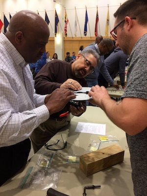 Employees from the DLA Troop Support Industrial Hardware supply chain participate in a Cross Function Day activity in the Bldg. 6 auditorium April 6. Personnel worked in small teams to construct military service insignia with hardware managed by the IH supply chain. The Cross Function Day event was designed to boost information-sharing across the supply chain's diverse units and functions.