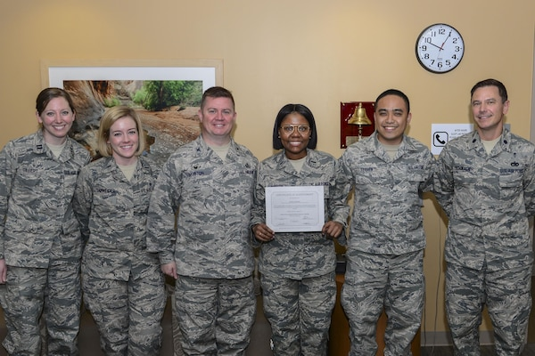 Air Force 1st Lt. Tyesha McBride, the 99th Mission Support Group's executive officer, is presented with a certificate of achievement for completing her cancer treatment at the Mike O'Callaghan Medical Center at Nellis Air Force Base, Nev., March 21, 2017. McBride was diagnosed with Hodgkin's lymphoma, which is a cancer of the lymphatic system. Air Force photo by Airman 1st Class Nathaniel Byrnes