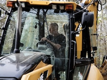 Carlos Procter, 11th Civil Engineer Squadron heavy equipment operator, drives a tractor-loader-backhoe in Clinton, Md., April 13, 2017. Procter and many other Joint Base Andrews members provided support in response to the 113th Wing, D.C. Air National Guard, F-16C Fighting Falcon incident that occurred approximately six miles southwest from JBA, April 5, 2017. (U.S. Air Force photo by Airman 1st Class Valentina Lopez)