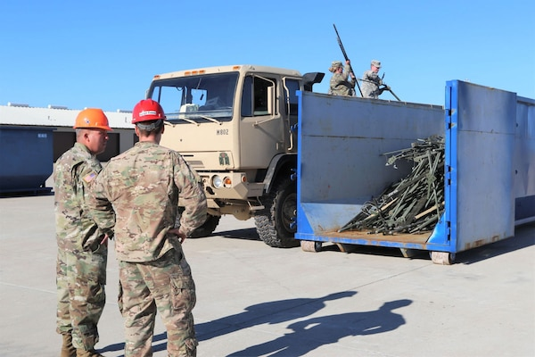 Soldiers from the 62nd ESB, 11th TTSB, recycle unserviceable military equipment as they dispose of a 20-foot container and a Tricon worth of materials during the surge event.