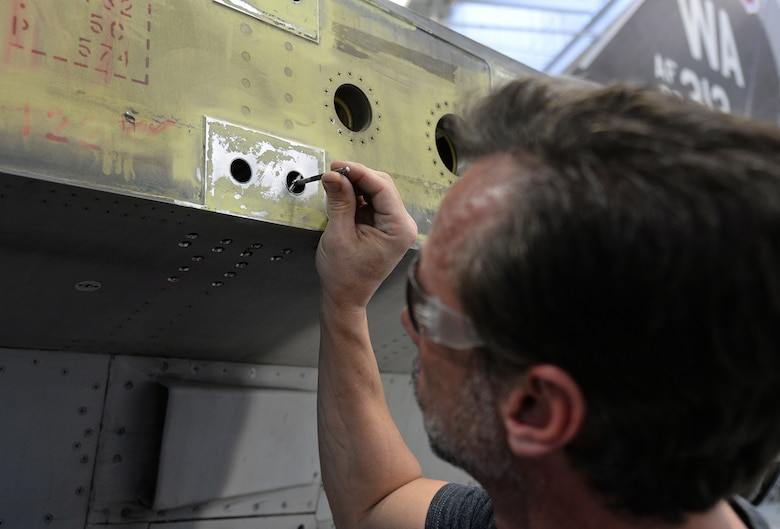 Mr. Ryan Wagstaff, 576 AMXS Machinist, uses a telescoping gauge while inspecting wing-attachment points. These inspections help determine whether the holes meet the required tolerance or new bushings are necessary. (U.S. Air Force Photo by Alex R. Lloyd)