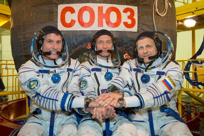 At the Integration Facility at the Baikonur Cosmodrome in Kazakhstan, Expedition 49 crewmembers Shane Kimbrough of NASA (left) and Sergey Ryzhikov (center) and Andrey Borisenko (right) of Roscosmos pose for pictures Sept. 9 in front of their Soyuz MS-02 spacecraft during a pre-launch training fit check. Kimbrough, Ryzhikov and Borisenko will launch Sept. 24, Kazakh time on the Soyuz MS-02 vehicle for a five-month mission on the International Space Station.