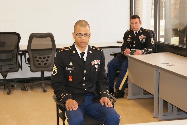 Staff Sgt. Ramon Abreu answers questions at the Command Sergeant Major Board held at Fort Devens, Massachusetts, April 3, 2017, as part of the 2017 Joint 80th Training Command and 99th Regional Support Command Best Warrior Competition .  Abreu's sponsor, Sgt. 1st Class Scott Baranek, quietly sits in the back and looks on.