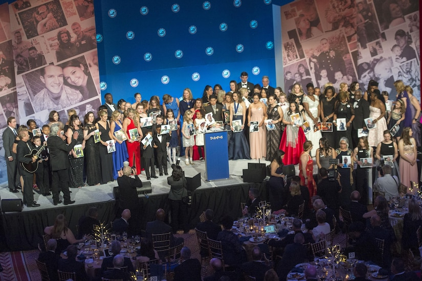 Surviving family members hold portraits of loved ones during the Tragedy Assistance Program for Survivors 2017 Honor Guard Gala in Washington, D.C., April 12, 2017. DoD photo by Navy Petty Officer 2nd Class Dominique Pineiro