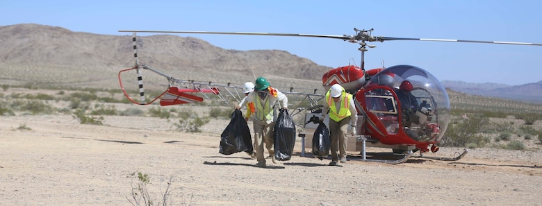 Employees from Natural Resources and Environmental Affairs, remove empty bins for desert tortoises from a helicopter during the Desert Tortoise translocation, April 10, 2017, which was facilitated by the Marine Corps Air Ground Combat Center, Twentynine Palms, Calif. The translocation, in accordance with the U.S. Fish and Wildlife Service-signed Biological Opinion, serves as a negotiated mitigation to support a congressionally mandated land expansion which, will afford the Combat Center the ability to conduct Large Scale Exercise training of a Marine Expeditionary Brigade-level force. (U.S. Marine Corps photo by Cpl. Medina Ayala-Lo)