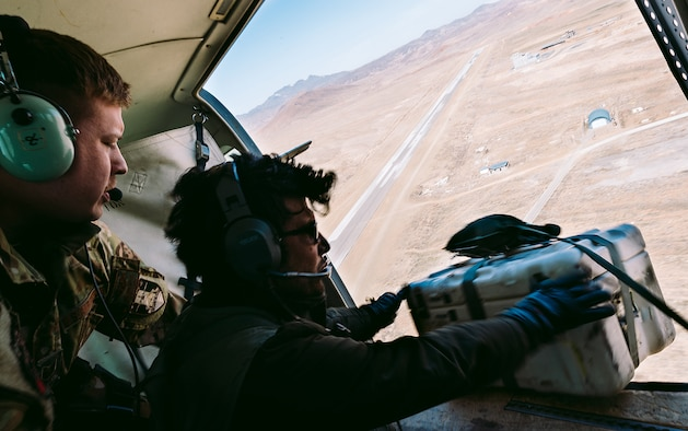 An Afghan Air Force member training with Train, Advise, Assist Command-Air, as part of Resolute Support Mission, works in tandem with an advisor to practice air drops near Kabul, Afghanistan, March 19, 2017. The TAAC-Air advisors foster working relationships and fortify confidence in the mission. (U.S. Air Force photo by Senior Airman Jordan Castelan)
