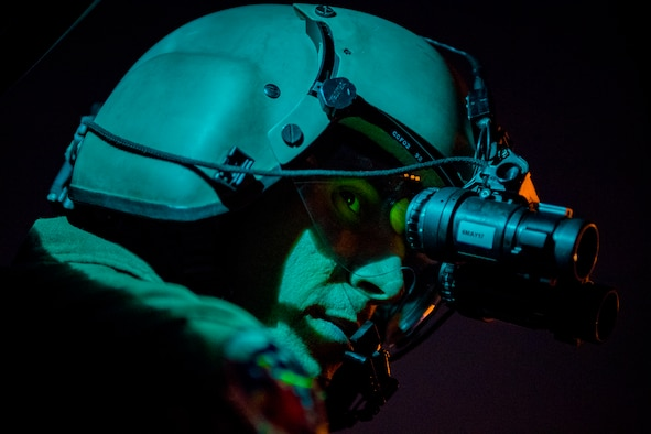 Staff Sgt. Nicholas A. Poe, a 459th Airlift Squadron special missions aviator, looks out the window of a UH-N1 Iroquois, through night vision goggles, during a night hoist training exercise April 4, 2017, in Tokyo. The aircrew trained with night vision goggles to prepare for missions that must be conducted at night. (U.S. Air Force photo/Airman 1st Class Donald Hudson)