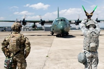 U.S. Air Force Staff Sgt. Courtney Hill, an aircraft maintainer assigned to the 621st Contingency Response Wing stationed at Joint Base McGuire-Dix-Lakehurst, N.J., and a South Korean air force Airman, marshal a South Korean air force C-130H during exercise Turbo Distribution 17-3, at Pohang Air Base, South Korea, April 10, 2017. (U.S. Air Force photo/Tech. Sgt. Gustavo Gonzalez)