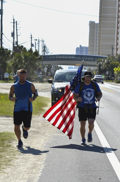 A local runner marches alongside Tech. Sgt. Doug Iredale, a special missions aviator with the 4th Special Operations Squadron, as part of the 6th Annual Air Commando Ruck March at Panama City Beach, Fla., April 13, 2017. The Air Commando Ruckers marched 450 miles from MacDill Air Force Base, to Hurlburt Field. (U.S. Air Force photo by Airman 1st Class Joseph Pick)