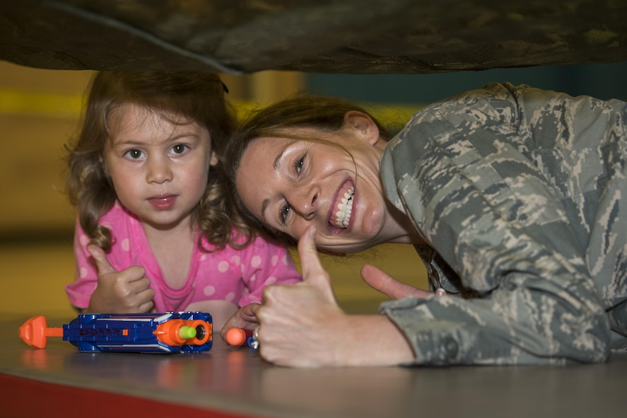Capt. Kathryn Escatel, Sheppard Family Advocacy program officer, participates in the family Nerf night with her 3-year-old daughter, Vaeda, at the Madrigal Youth Center, April 13, 2017. The Nerf night was held to encourage families to unplug from electronic devices and spend time bonding as families. (U.S. Air Force photo by Staff Sgt. Kyle E. Gese)