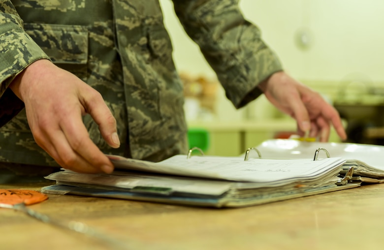 Senior Airman Mark Lee, an Electrical and Environmental craftsman assigned to the 28th Maintenance Squadron, opens a binder inside the E&E back shop at Ellsworth Air Force Base, S.D, April 12, 2017. While troubleshooting components of the B-1 bomber, E&E Airmen sign in parts, assess the problem, order equipment and fix the parts as necessary. (U.S. Air Force photo by Airman 1st Class Randahl J. Jenson)